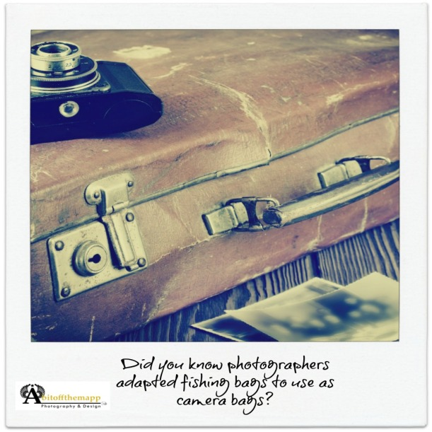 Old cracked stained suitcase with camera in vintage colors